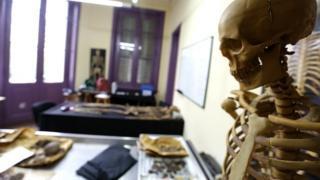 Esqueleto de plástico en primer plano y un laboratorio forense de fondo.