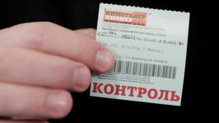 """A man holds a ticket of the """"Death of Stalin"""" movie, which was banned from being shown in cinemas of the country on January 24, as he attends its screening at the Pioner Cinema in Moscow, Russia"""