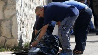 Israeli medics carry away the body of a Palestinian man who attempted to stab a soldier in the East Jerusalem Jewish settlement of Armon Hanatsiv, adjacent to the Palestinian neighbourhood of Jabal Mukaber, on October 17, 2015