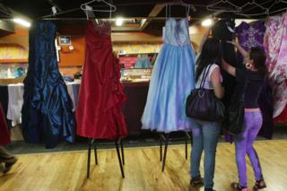 Women look at prom dresses at Project Prom, an event offering free dresses, handbags, shoes and accessories to high school students on May 22, 2009 in New York City.