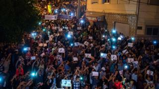 Demonstrators hold pictures of Nasser Zafzafi during a demonstration in the northern city of al-Hoceima on May 30, 2017