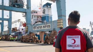 Man in Turkish Red Crescent shirt watching Lady Leyla ship unload