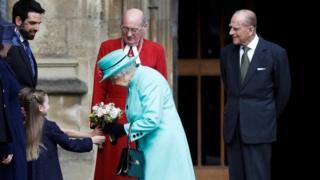 The Queen receives some flowers from a young girl