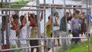 Asylum-seekers look through a fence at the Manus Island detention centre in Papua brand new Guinea