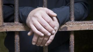 Man's hands behind jail bars