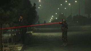 Afghan security officer trains a laser sight on a target off-camera, while a man in civilian clothing can be seen talking on the phone nearby.
