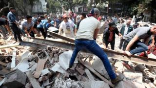 Rescuers dey help clear building wey collapse