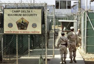 In this June 27, 2006 file photo, US military guards walk within Camp Delta military-run prison, at the Guantanamo Bay U.S. Naval Base, Cuba.