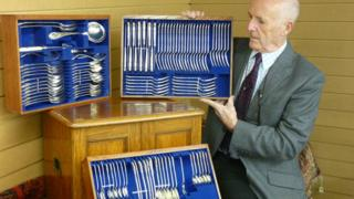 Auctioneer David Roger Jones with the collection of cutlery