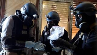 A U.N. chemical weapons expert, wearing a gas mask, holds a plastic bag containing samples from one of the sites of an alleged chemical weapons attack in the Ain Tarma neighbourhood of Damascus in this August 29, 2013