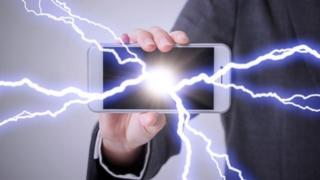 Una persona que sostiene un teléfono, del cual salen rayos