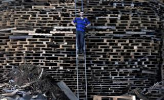 'Hurka' the chief architect and builder of the Craigyhill bonfire takes a break from stacking pallets to pose with his creation whilst balancing on a ladder on July 10, 2017 in Larne,
