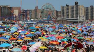 Люди відпочивають на пляжі Коні-Айленда ,Бруклін, Нью-Йорк.