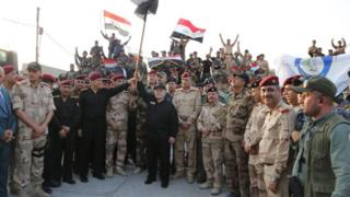 Photograph posted by Iraqi prime minister's office showing Haider al-Abadi (centre) waving a national flag after declaring victory in the battle for Mosul (10 June 2017)