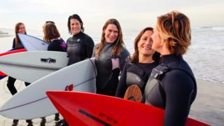 Mulheres surfistas posam na praia