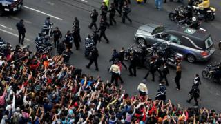 Fans take pictures of hearse carrying ashes of late Mexican singer Juan Gabriel as its arrives outside the Palace of Fine Arts in Mexico City, 5 September 2016