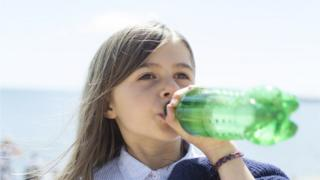 A young girl drinks a fizzy drink