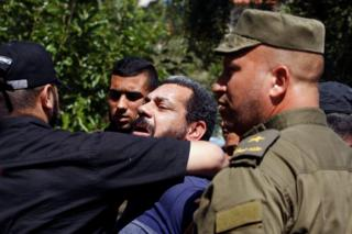 Members of Palestinian security forces loyal to Hamas escort a prisoner in Gaza City, 21 May