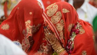 Muslim brides, veiled in red, speak during a mass wedding ceremony in 2015