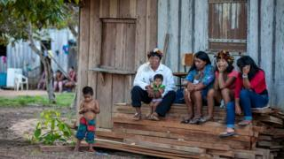 A group of members of the Cinta Larga sit in front of a house