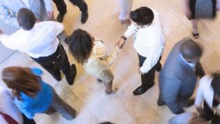 Mujer negra saludándose con un hombre blanco.