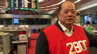 Trader Christopher Cheung stands on the floor of the Hong Kong stock exchange