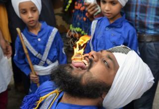 Un nihang, de la orden de guerreros armados sij, sostiene un cubo inflamable en su lengua en Amritsar, en India.