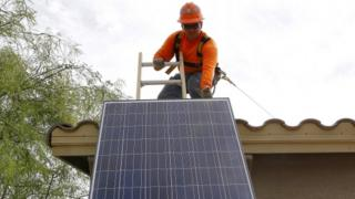 Worker installing solar panel on roof