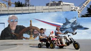 People pass a mural of Putin at the wheel of a ship