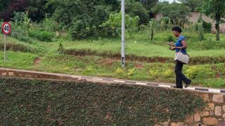 rwandan woman checks her mobile phone while walking up a slope