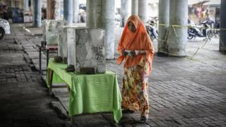 An Indonesian woman casts her vote at a polling station under a highway bridge in Jakarta, Indonesia, 19 April 2017