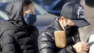 A woman and a man on a scooter wear protective masks in Beijing on 18 December, 2015