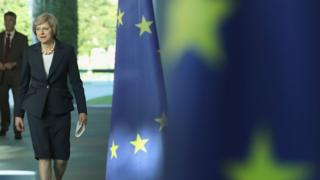 British Prime Minister Theresa May walks past European Union flags as she and German Chancellor Angela Merkel (not pictured) arrive to speak to the media following talks at the Chancellery on July 20, 2016 in Berlin, Germany.