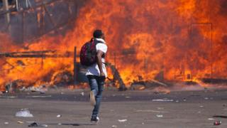 Zimbabwe's opposition supporters set up a burning barricade as they clash with police during a protest for electoral reforms on 26 August 2016 in Harare, Zimbabwe