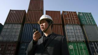 A worker monitors the loading of shipping containers in Hubei province in China