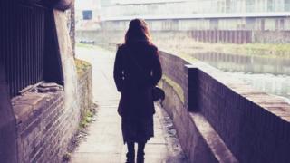 امرأة تسير في الشارع ويبدو أنها تشك في أن أحدا يسير خلفها