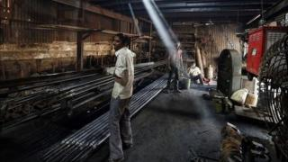 A worker carries an iron pipe inside a metal fabrication workshop in an industrial area of Mumbai