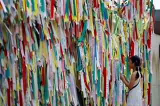 A girl looks at a fence covered with pastel ribbons
