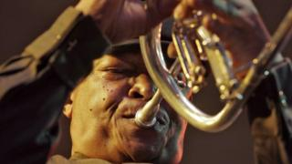 South African jazz maestro Hugh Masakela playing trumpet