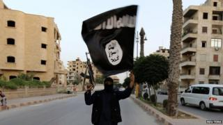 A lone armed and masked Islamic State militant waving an Isis flag on a deserted street in Raqqa, June 2014