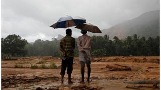 Two Sri Lankan landslide survivors stand on mud, holding their sandals and umbrellas, looking at a large area of mud after a landslide in Elangipitiya village in Aranayaka. Photo taken on 18 May 2016.