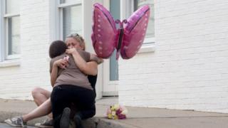 Mulher chora em frente a flores no local onde uma mulher morreu e 19 pessoas ficaram feridas, em Charlottesville, EUA