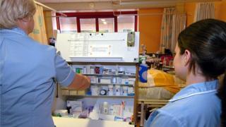 Nursing staff dispensing drugs from a trolley on a hospital warn