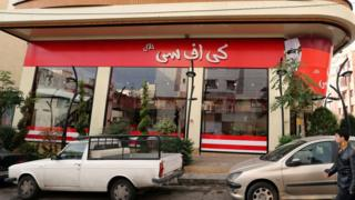 """A man walks past the fried chicken shop """"KFC Halal"""", after it was closed by Iranian police"""