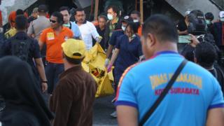 Petugas mengangkut jasad dari salah seorang korban serangan di Gereja Pantekosta, Surabaya, Minggu (13/05).
