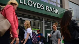 Shoppers walk past Lloyds bank branch