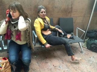 Flight attendant Nidhi Chaphekar (R) reacts in the moments following a suicide bombing at Brussels Zaventem airport on 22 March 2016, in Brussels, Belgium.