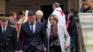 Mayor of Trebes Eric Menassi (centre) and his wife Director of Super U supermarket Samia Menassi (right) leave the remembrance service at the Saint Etienne Church in Trebes, southwest France.