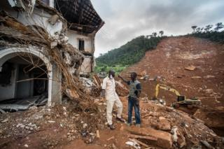 Alfred Johnny talks to friend beside the broken house and mudslide