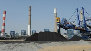 Workers use heavy machinery to sift through coal at the Adani Power company thermal power plant at Mundra